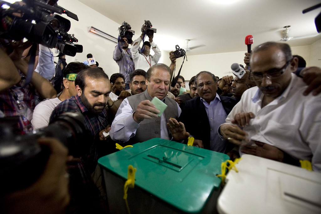 . Former Prime Minister Nawaz Sharif, center, casts his vote at a polling station during the country\'s parliamentary election in Lahore, Pakistan, Saturday, May 11, 2013. Defying the danger of militant attacks, Pakistanis streamed to the polls Saturday for a historic vote pitting a former cricket star against a two-time prime minister and an unpopular incumbent. But attacks that killed and wounded dozens of people underlined the risks many people took just casting their ballots.(AP Photo/Anjum Naveed)