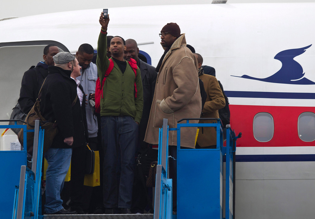 ". U.S. basketball player Jerry Dupree, center, uses a mobile camera to take a photograph as he and fellow players including former NBA player Vin Baker, right, arrive at the international airport in Pyongyang, North Korea, Monday, Jan. 6, 2014. Dennis Rodman arrived in the North Korean with a squad of former basketball stars in what Rodman calls ""basketball diplomacy,\"" although U.S. officials have criticized his efforts. (AP Photo/Kim Kwang Hyon)"