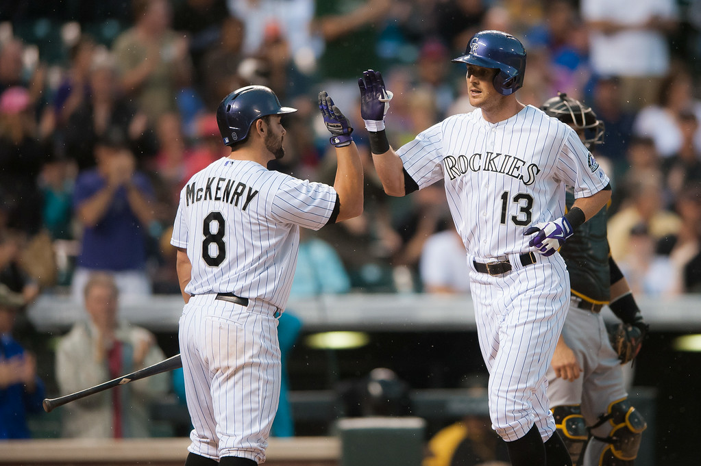 . Drew Stubbs #13 of the Colorado Rockies celebrates a fourth inning leadoff home run hit against the Pittsburgh Pirates with Michael McKenry #8 at Coors Field on July 26, 2014 in Denver, Colorado.  (Photo by Dustin Bradford/Getty Images)