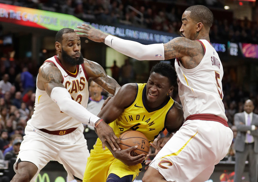 . Indiana Pacers\' Victor Oladipo (4) drives between Cleveland Cavaliers\' LeBron James (23) and JR Smith (5) in the second half of an NBA basketball game, Friday, Jan. 26, 2018, in Cleveland. The Cavaliers won 115-108. (AP Photo/Tony Dejak)