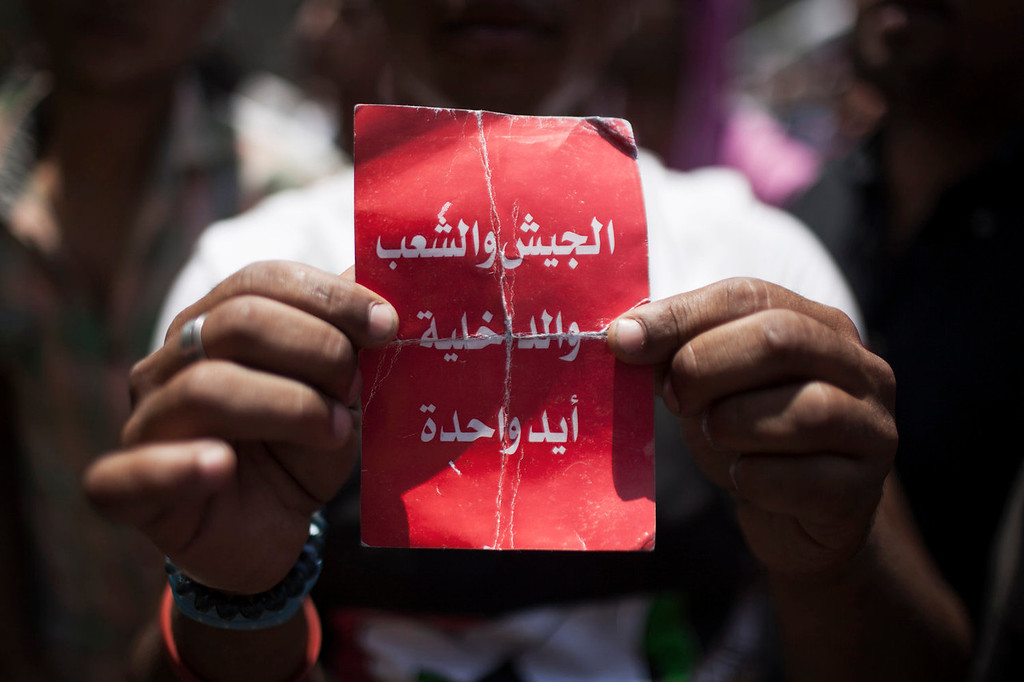 ". An Egyptian protester holds a card that says ""army, people and police - one hand\"" during a spontaneous demonstration against Egypt\'s Islamist President Mohammed Morsi in Tahrir Square in Cairo, Saturday, June 29, 2013. Thousands of supporters and opponents of Egypt\'s embattled Islamist president are holding rival sit-ins on the eve of what are expected to be massive opposition-led protests aimed at forcing Mohammed Morsi\'s ouster.  (AP Photo/Manu Brabo)"