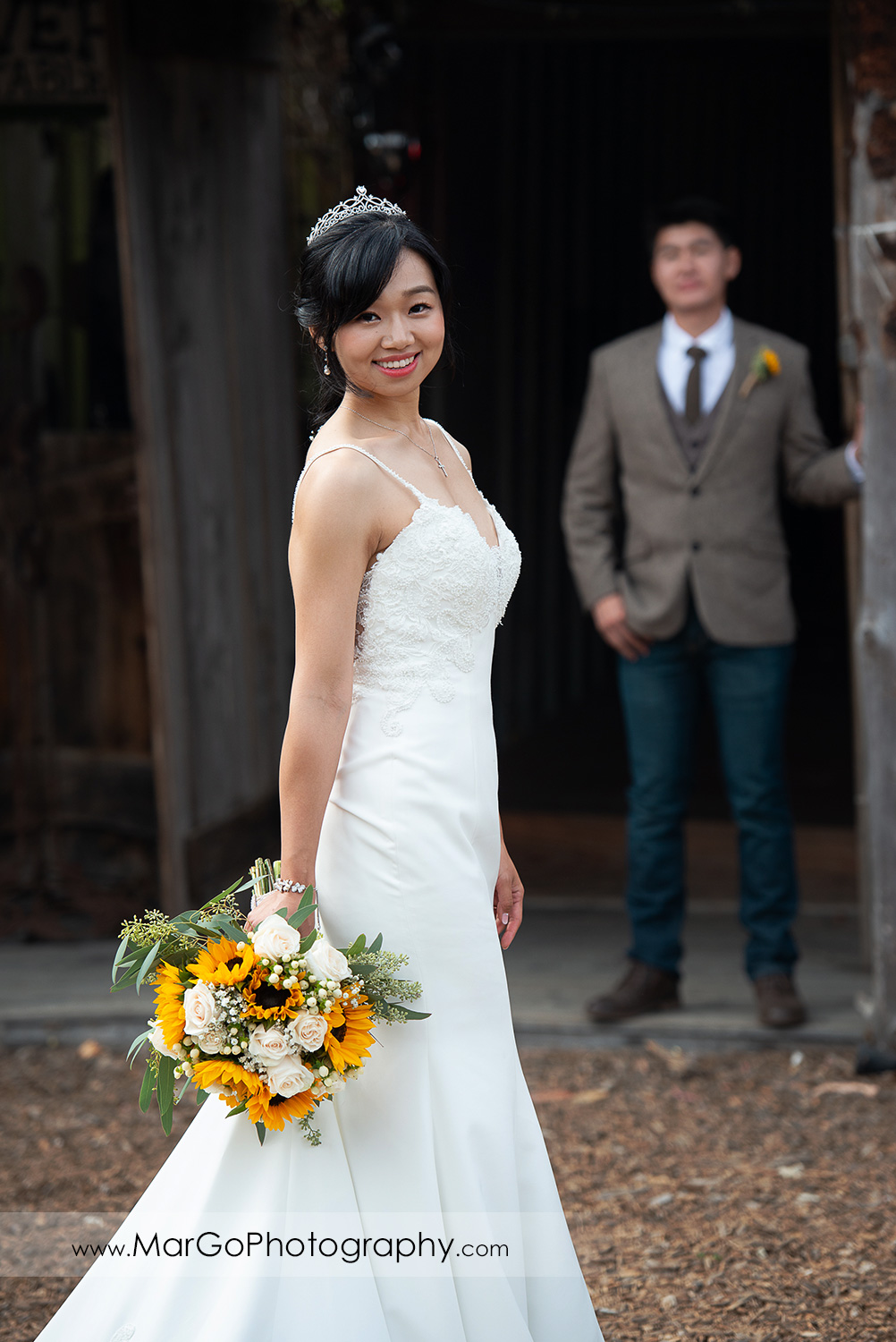 portrait of the bride holding yellow flower bouquet with groom in background at Long Branch Saloon & Farms in Half Moon Bay