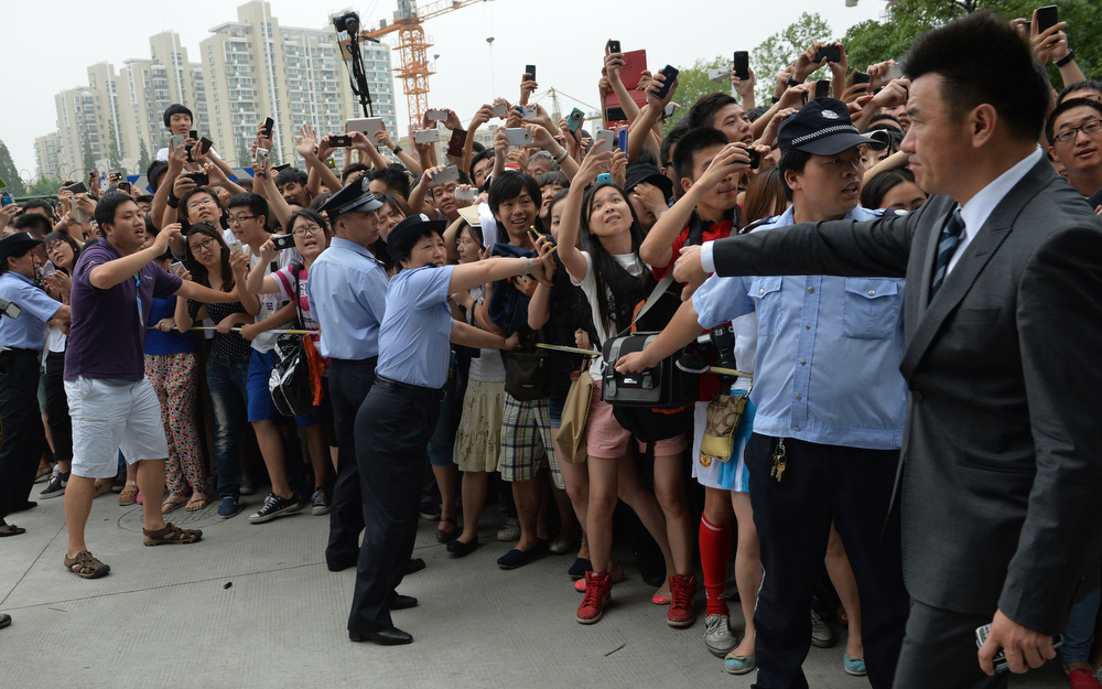 """. A huge crowd gathers to see football superstar David Beckham at Tonji University in Shanghai on June 20, 2013. Football superstar David Beckham\'s visit to China turned \""""chaotic\"""" on Thursday after at least five people were hurt in a stampede as fans rushed to see him, local media and an AFP photographer at the scene said.  PETER PARKS/AFP/Getty Images"""