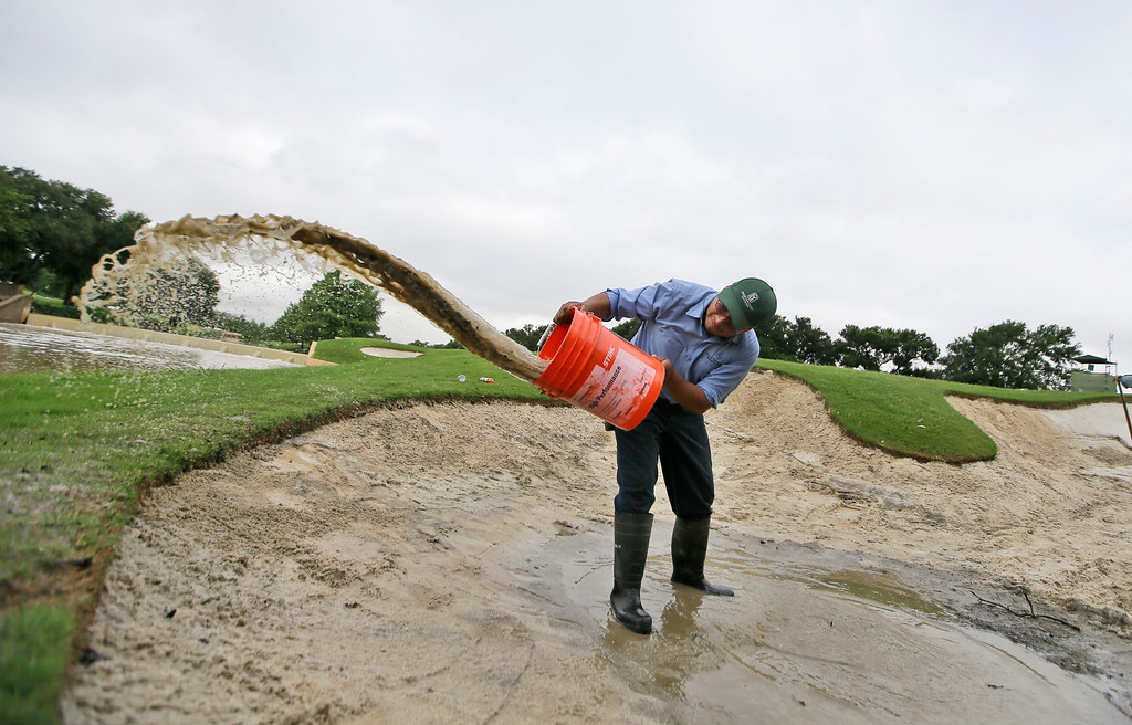 . Antonio Rodriguez scoops water out of the sand trap on the ninth green before the start of the second round of the Byron Nelson golf tournament, Friday, May 29, 2015, in Irving, Texas.  Heavy overnight rains delayed the start of play. (AP Photo/LM Otero)
