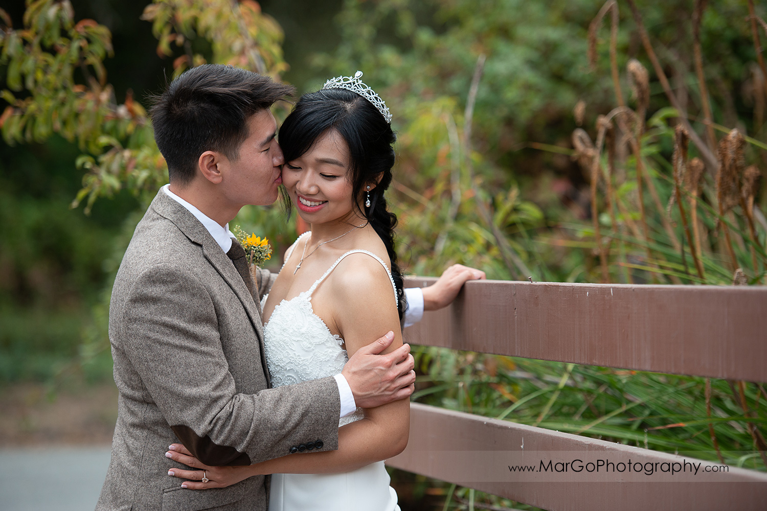 groom kissing bride's cheek on wooden fence at Long Branch Saloon & Farms in Half Moon Bay