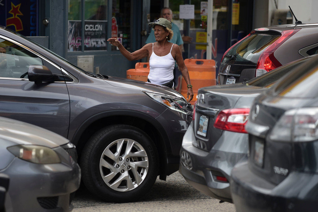 . A woman directs drivers lining up to buy gasoline at a gas station one day before the forecasted arrival of Hurricane Maria in San Juan, Puerto Rico, Tuesday, Sept. 19, 2017. Authorities in the U.S. territory of Puerto Rico, which faces the possibility of a direct hit, warned that people in wooden or flimsy homes should find safe shelter before the storm�s expected arrival there on Wednesday. (AP Photo/Carlos Giusti)