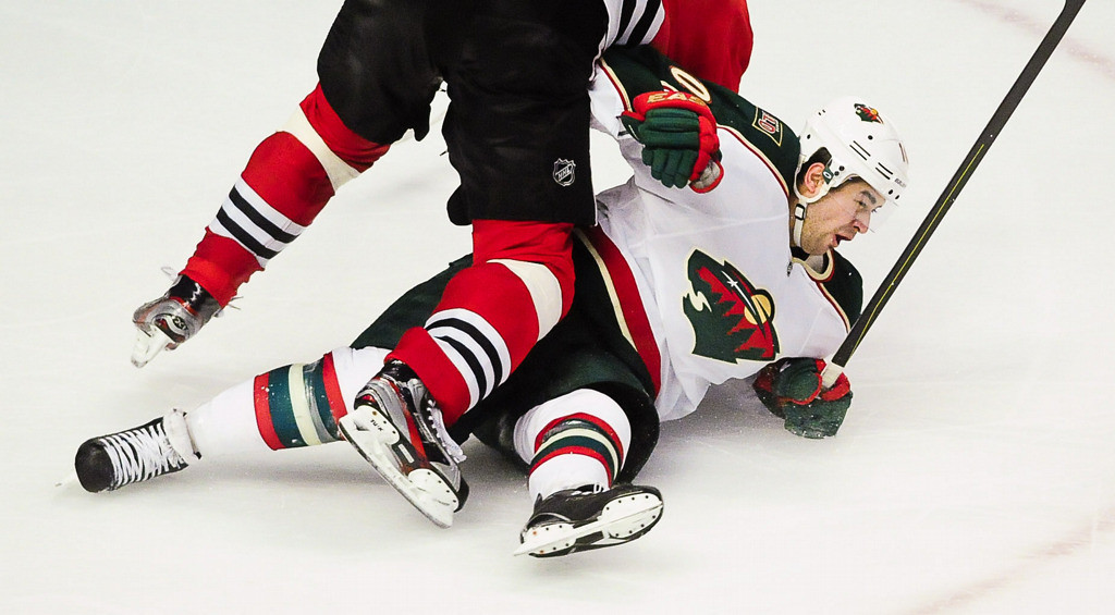 . Minnesota Wild right wing Devin Setoguchi is knocked to the ice by Chicago Blackhawks defenseman Michal Rozsival in overtime. (Pioneer Press: Ben Garvin)