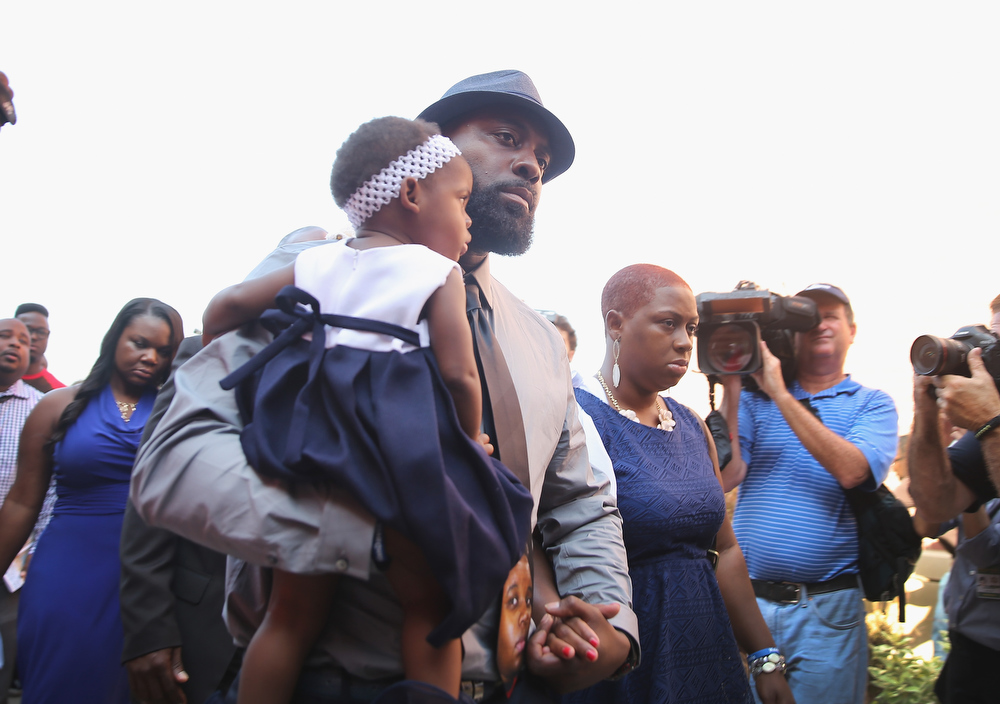 Description of . Michael Brown Sr. arrives at Friendly Temple Missionary Baptist Church for the funeral of his son Michael Brown Jr. on August 25, 2014 in St. Louis, Missouri. Michael Brown, an 18 year-old unarmed teenager, was shot and killed by Ferguson Police Officer Darren Wilson in the nearby town of Ferguson, Missouri on August 9. His death caused several days of violent protests along with rioting and looting in Ferguson.  (Photo by Scott Olson/Getty Images)