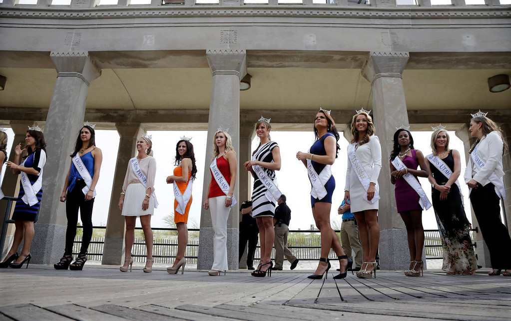 . Miss America contestants wait to be introduced after arriving in Atlantic City, Tuesday, Sept. 3, 2013. The Miss America pageant is back in the city where it began, six years after spurning the city for Las Vegas. The pageant held a welcoming ceremony Tuesday for the 53 contestants, one from each state plus the District of Columbia, Puerto Rico and the U.S. Virgin n Islands. The contestants filed out of Boardwalk Hall, where the competition will begin next week and culminate days later, and walked across the Boardwalk to a stage. (AP Photo/Mel Evans)