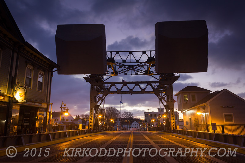 In the pre-dawn, the historic Mystic drawbridge stands as a dark silhouette against the cool sky.   The Mystic Drawbridge is a historic drawbridge that spans the Mystic River in downtown Mystic, CT. Built in 1920 by the J.E. FitzGerald Construction Company of New London, CT, this bridge is a historic landmark and a centerpiece of the Mystic community.  Prints and framed artwork of this image are available from our store on FAA, here:  http://fineartamerica.com/featured/mystic-sky-bridge-kirkodd-photography-of-new-england.html?newartwork=true