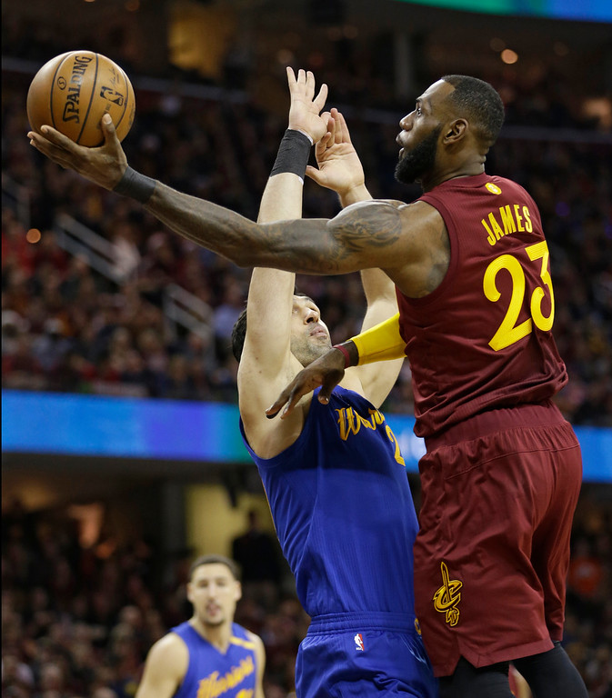 . Cleveland Cavaliers\' LeBron James (23) drives against Golden State Warriors\' Zaza Pachulia (27), from Republic of Georgia, in the first half of an NBA basketball game, Sunday, Dec. 25, 2016, in Cleveland. (AP Photo/Tony Dejak)