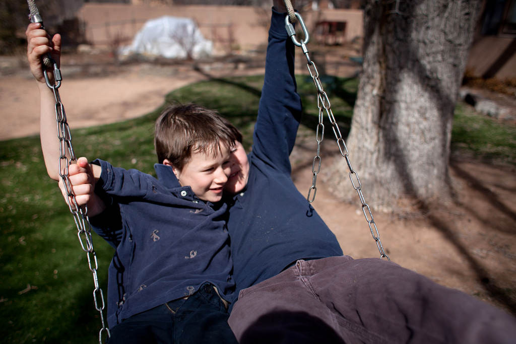 . Keenan and Liam Downey enjoy their swing on a patch of artificial grass in their back yard. The green spot  provides a pleasant setting for patio furniture -- well shaded in season by an 80-year-old Siberian elm -- as well as a place for the boys to play. (Special to the Pioneer Press: Mark Holm)
