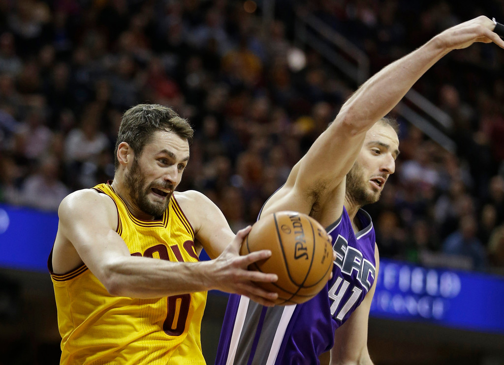 . Cleveland Cavaliers\' Kevin Love (0) grabs a rebound ahead of Sacramento Kings\' Kosta Koufos (41) during the first half of an NBA basketball game, Wednesday, Jan. 25, 2017, in Cleveland. (AP Photo/Tony Dejak)