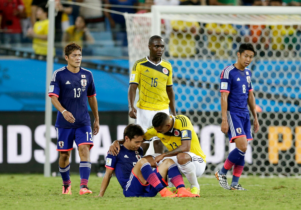 . Colombia\'s Fredy Guarin, right comforts Japan\'s Yuto Nagatomo after the group C World Cup soccer match between Japan and Colombia at the Arena Pantanal in Cuiaba, Brazil, Tuesday, June 24, 2014. Colombia won 4-1.(AP Photo/Dolores Ochoa)