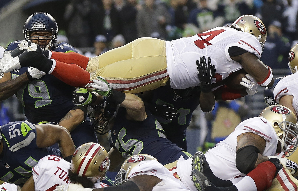 . San Francisco 49ers\' Anthony Dixon dives into the end zone for a touchdown run during the first half of the NFL football NFC Championship game against the Seattle Seahawks Sunday, Jan. 19, 2014, in Seattle. (AP Photo/Marcio Jose Sanchez)
