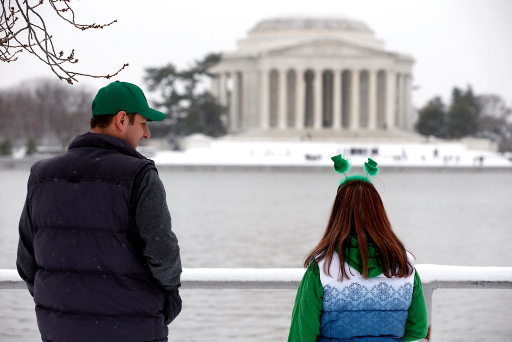 . Craig Hyatt, left, and his wife Shannon Hyatt, both from Toronto, look toward the Jefferson Memorial after a St. Patrick\'s Day winter storm, Monday, March 17, 2014 in Washington. Snow has been falling in parts of the Mid-Atlantic and Northeast as winter-weary motorists faced another potentially treacherous commute Monday morning, just days before the start of spring. (AP Photo/Alex Brandon)