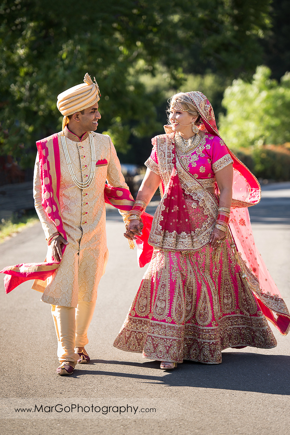 Indian bride and groom in golden and pink outfits walking at Elliston Vineyards in Sunol