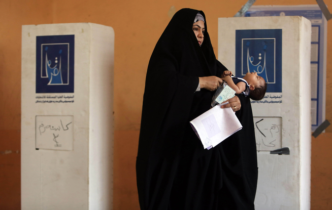 Description of . An Iraqi woman prepares to cast her vote for parliamentary elections as she carries her daughter at a polling station in Basra, Iraq's second-largest city, 340 miles (550 kilometers) southeast of Baghdad, Iraq, Wednesday, April 30, 2014. Iraq is holding its third parliamentary elections since the U.S.-led invasion that toppled dictator Saddam Hussein. More than 22 million voters are eligible to cast their ballots to choose 328 lawmakers out of more than 9,000 candidates. (AP Photo/ Nabil al-Jurani)
