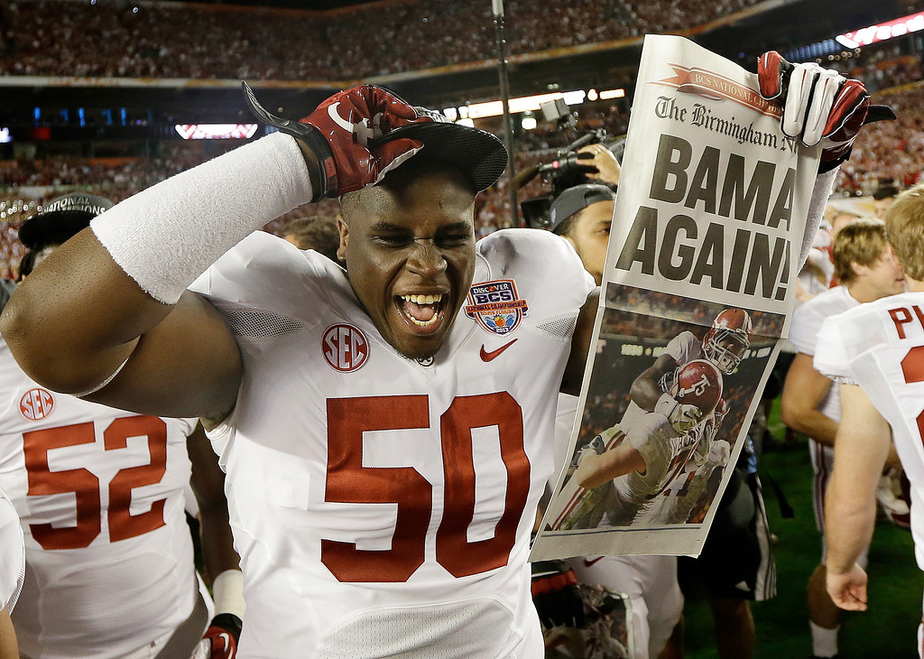 . Alabama defensive lineman Alphonse Taylor (50) holds up a newspaper after the BCS National Championship college football game Monday, Jan. 7, 2013, in Miami. Alabama won 42-14. (AP Photo/David J. Phillip)