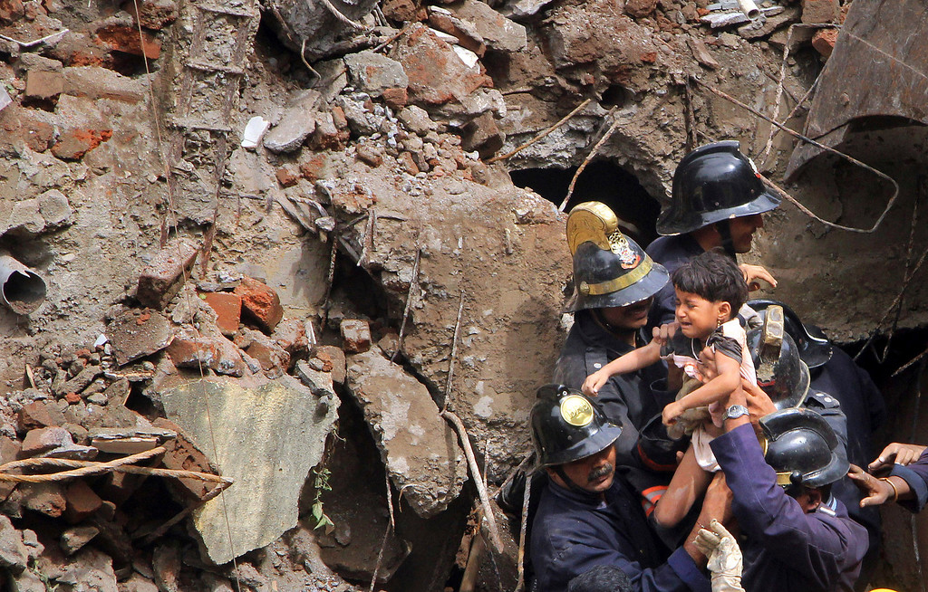 . Indian Fire officials rescue a girl from debris of a collapsed building in Mumbai, India, Friday, Sept. 27, 2013. . (AP Photo)