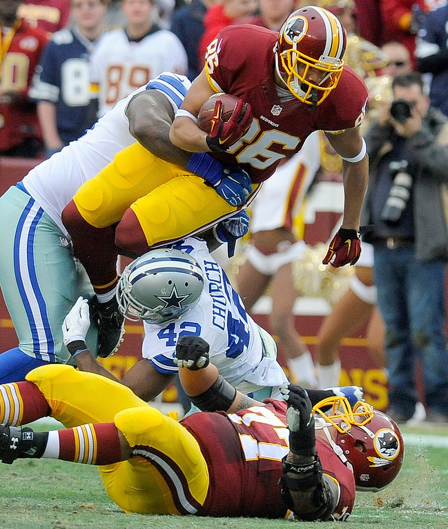 . Washington Redskins tight end Jordan Reed (86) is stopped by Dallas Cowboys defensive tackle Henry Melton, left, and strong safety Barry Church (42) during the first half of an NFL football game in Landover, Md., Sunday, Dec. 28, 2014. (AP Photo/Richard Lipski)