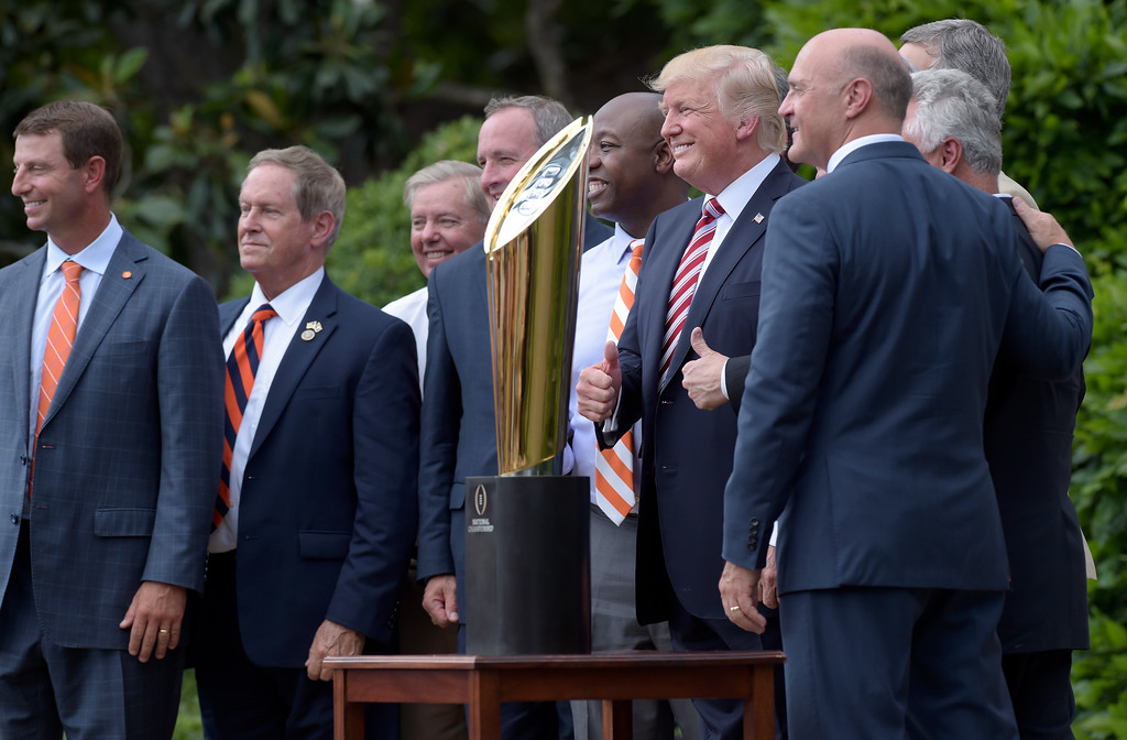 . President Donald Trump poses for a photo during a ceremony on the South Lawn of the White House in Washington, Monday, June 12, 2017, honoring the 2016 NCAA Football National Champions Clemson University Tigers. From left are, Clemson head football coach Dabo Swinney, Rep. Joe Wilson, R-S.C., Sen. Lindsey Graham, R-S.C., Rep. Jeff Duncan, R-S.C., Sen. Tim Scott, R-S.C., the president and Clemson University President Jim Clements. (AP Photo/Susan Walsh)