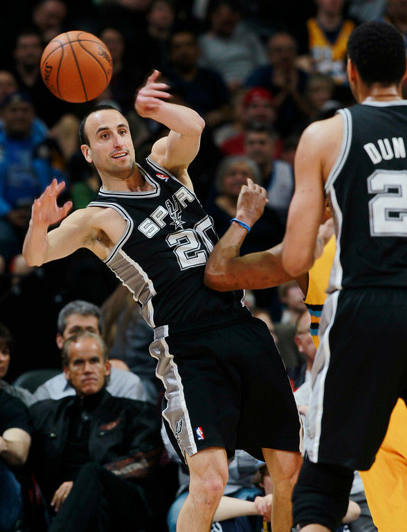 . San Antonio Spurs guard Manu Ginobili (20), of Argentina, passes the ball around Denver Nuggets guard Randy Foye to Spurs center Tim Duncan in the first quarter of an NBA basketball game in Denver, Friday, March 28, 2014. (AP Photo/David Zalubowski)