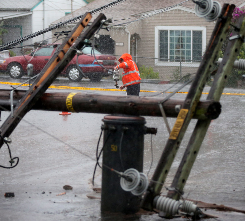 . A PG&E worker picks up parts from a power line after a tree knocked down a utility pole along Tanager Avenue on Thursday, Dec. 11, 2014, in San Leandro, Calif.   (Aric Crabb/Bay Area News Group)