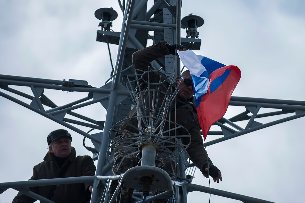. Pro-Russian forces hang up a Russian flag after seizing the Ukrainian corvette Khmelnitsky in Sevastopol, Crimea, Thursday, March 20, 2014.  (AP Photo/Andrew Lubimov)