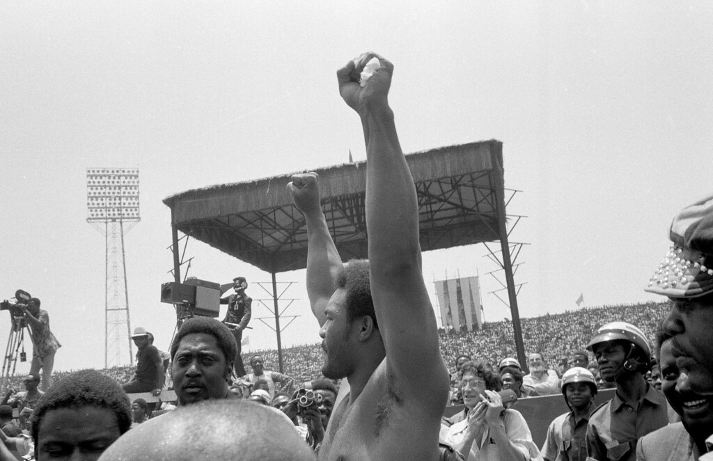 . Heavyweight champion George Foreman raises both fists in salute to crowd during opening ceremonies Sunday at the arena in Zaire where he and challenger Muhammad Ali will meet for the world heavyweight crown Oct. 30. Foreman took his jacket off while walking around the infield of the stadium.  (AP Photo/Horst Faas)