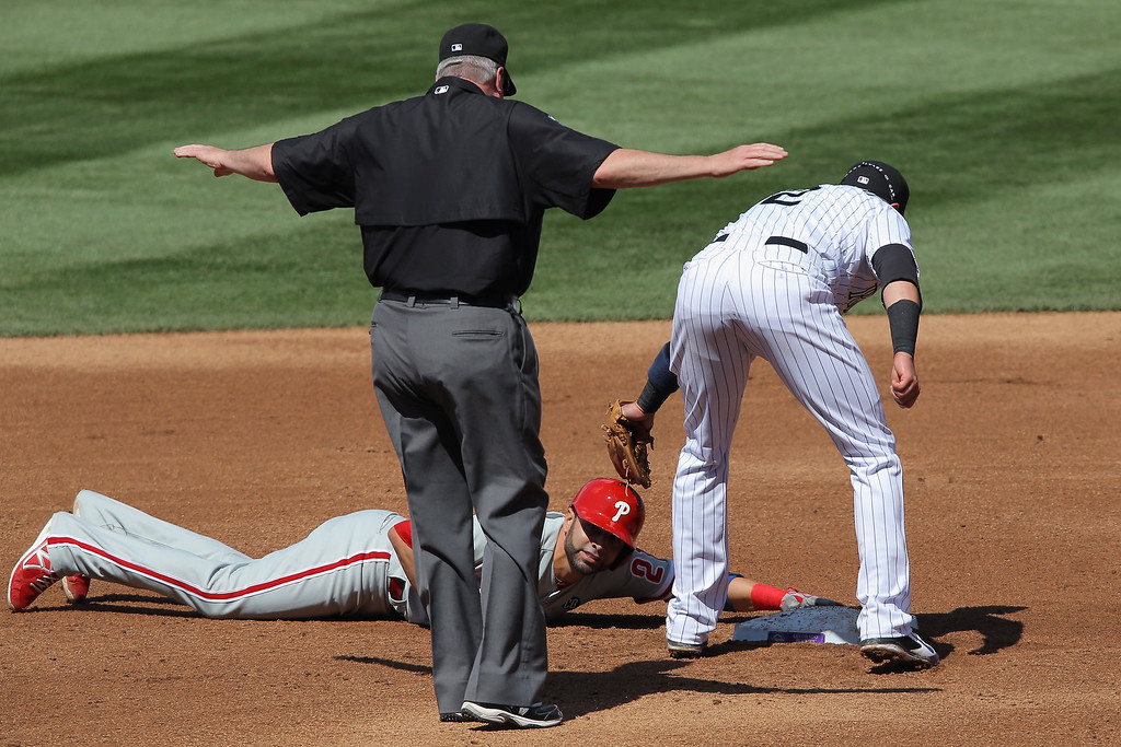 . Wil Nieves #21 of the Philadelphia Phillies slides safely into second base with a double as shortstop Troy Tulowitzki #2 of the Colorado Rockies makes the late tag and umpire Todd Tichenor makes the call in the second inning at Coors Field on April 20, 2014 in Denver, Colorado.  (Photo by Doug Pensinger/Getty Images)