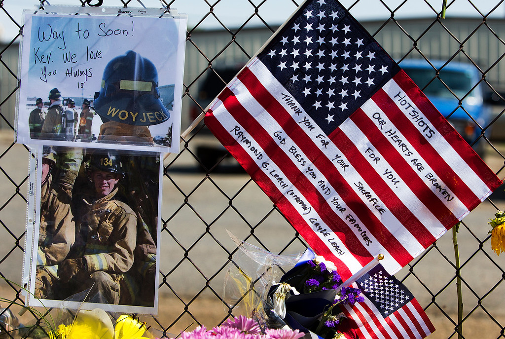 . Mementos are posted on a fence outside Fire Station 7 in Prescott, Ariz. on Tuesday, July 2, 2013 in a makeshift memorial for the 19 Granite Mountain Hotshots who were killed by an out-of-control blaze near Yarnell, Ariz. on Sunday. (AP Photo/The Arizona Republic, Tom Tingle)