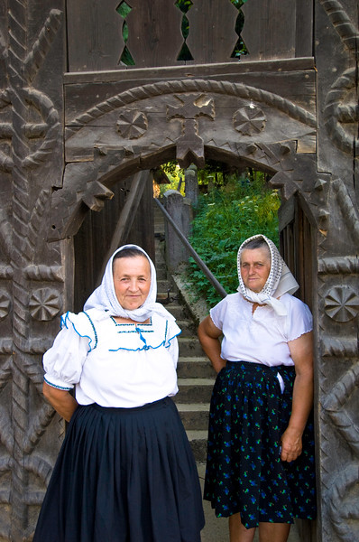 Local women by traditional wooden gate, Budesti, Maramures, Roma