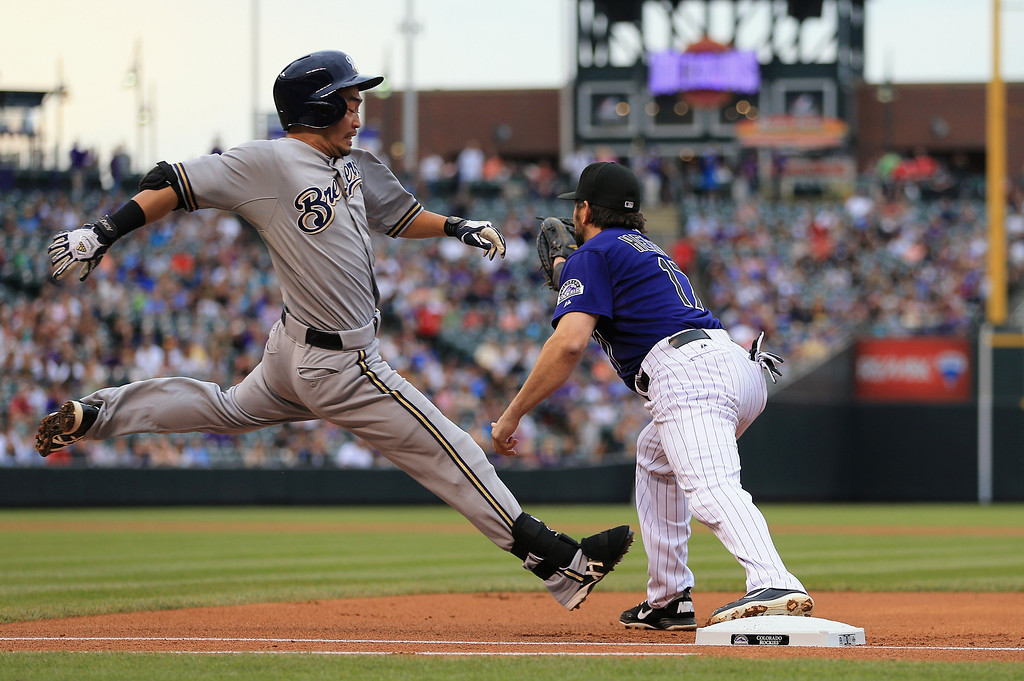 . DENVER, CO - JULY 27:  First baseman Todd Helton #17 of the Colorado Rockies gets the put out on a sacrifice bunt by Norichika Aoki #7 of the Milwaukee Brewers in the first inning at Coors Field on July 27, 2013 in Denver, Colorado.  (Photo by Doug Pensinger/Getty Images)