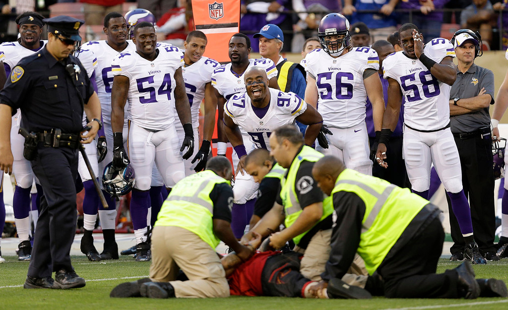 . Vikings defensive end Everson Griffen (97) and teammates enjoy one of their few highlights as San Francisco Police officers and security grab a fan who ran onto the field during the fourth quarter. (AP Photo/Marcio Jose Sanchez)