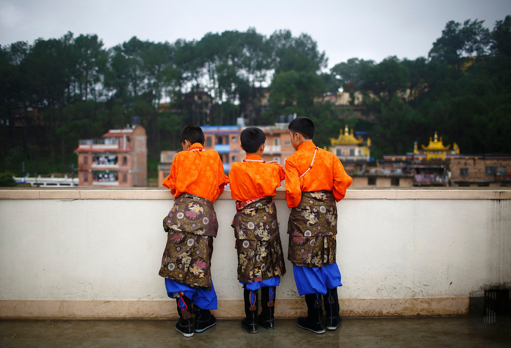 . Tibetan boys dressed in traditional costumes look down from the roof of a monastery during celebrations of the 78th birthday of exiled spiritual leader Dalai Lama in Kathmandu July 6, 2013. During last month\'s visit of Chinese State Councilor Yang Jiechi, Chairman of the Interim Election Council Khil Raj Regmi said Nepal is firmly committed to the One-China Policy and reaffirmed its stand that the territory of Nepal will not be allowed to be used for any activities against China. Nepal ceased issuing refugee papers to Tibetans in 1989 and recognizes Tibet to be a part of China. REUTERS/Navesh Chitrakar