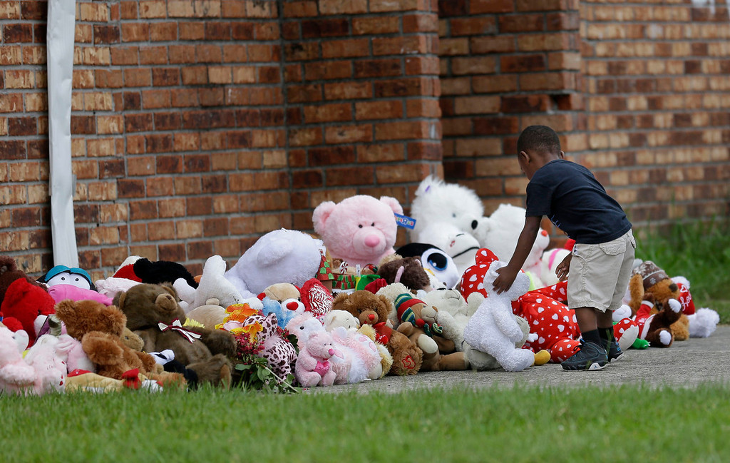 . Fleming Clark, 2, places a teddy bear at a makeshift memorial near a trash bin where the body of missing 6-year-old Ahlittia North was said to have been found in Harvey, La., Tuesday, July 16, 2013. Her mother , Lisa North, says Jefferson Parish authorities have found the body of her daughter in a Harvey trash bin. Ahlittia disappeared from her apartment late Friday night or early Saturday morning. North\'s husband Albert Hill said they were told the body was found in a trash bin not far from their apartment. (AP Photo/Gerald Herbert)