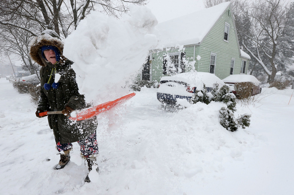 . Peggy Udden, of Norwood, Mass., shovels her driveway in Norwood, Wednesday, Feb. 5, 2014. Six to 12 inches of snow is expected around Boston, with 3 to 6 inches in southeastern areas before changing to sleet and rain Wednesday. (AP Photo/Steven Senne)