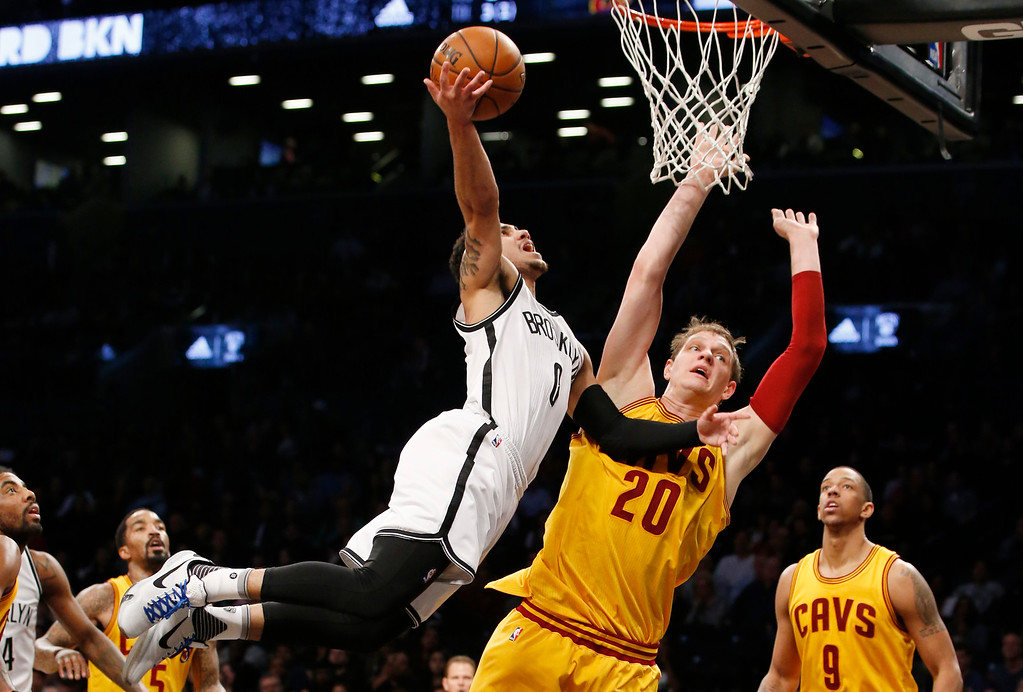. Brooklyn Nets guard Shane Larkin (0) shoots over Cleveland Cavaliers center Timofey Mozgov (20) in the second half of an NBA basketball game, Thursday, March 24, 2016, in New York. Larkin had 16 points as the Nets beat the Cavaliers 104-95. (AP Photo/Kathy Willens)