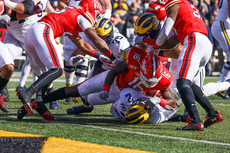 Maryland LB Ayinde Eley tackles Michigan QB Shea Patterson inches short of the goal line.