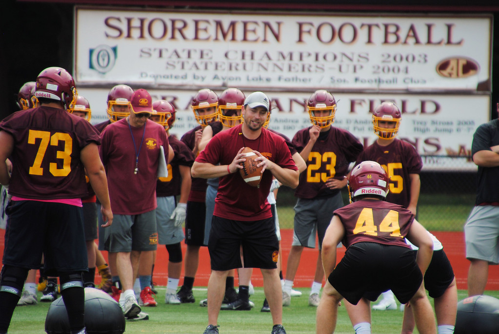 . Jon Behm - The Morning Journal<br> Avon Lake coach Matt Kostelnik runs a drill during Avon Lake\'s first day of football practice on July 30.