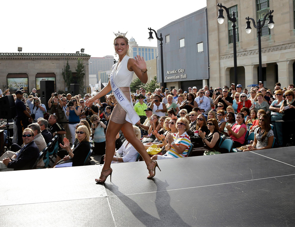 . Miss New Jersey Cara McCollum waves as she walks on a runway as Miss America contestants arrive in Atlantic City, N.J. on Tuesday, Sept. 3, 2013. The Miss America pageant is back in the city where it began, six years after spurning the city for Las Vegas. The pageant held a welcoming ceremony Tuesday for the 53 contestants, one from each state plus the District of Columbia, Puerto Rico and the U.S. Virgin n Islands. The contestants filed out of Boardwalk Hall, where the competition will begin next week and culminate days later, and walked across the Boardwalk to a stage. (AP Photo/Mel Evans)