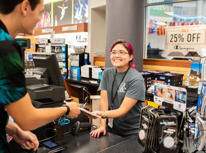 Brandy Leos (right) assists Travis Chudej with purchasing his textbook at the Barnes & Noble University Bookstore.