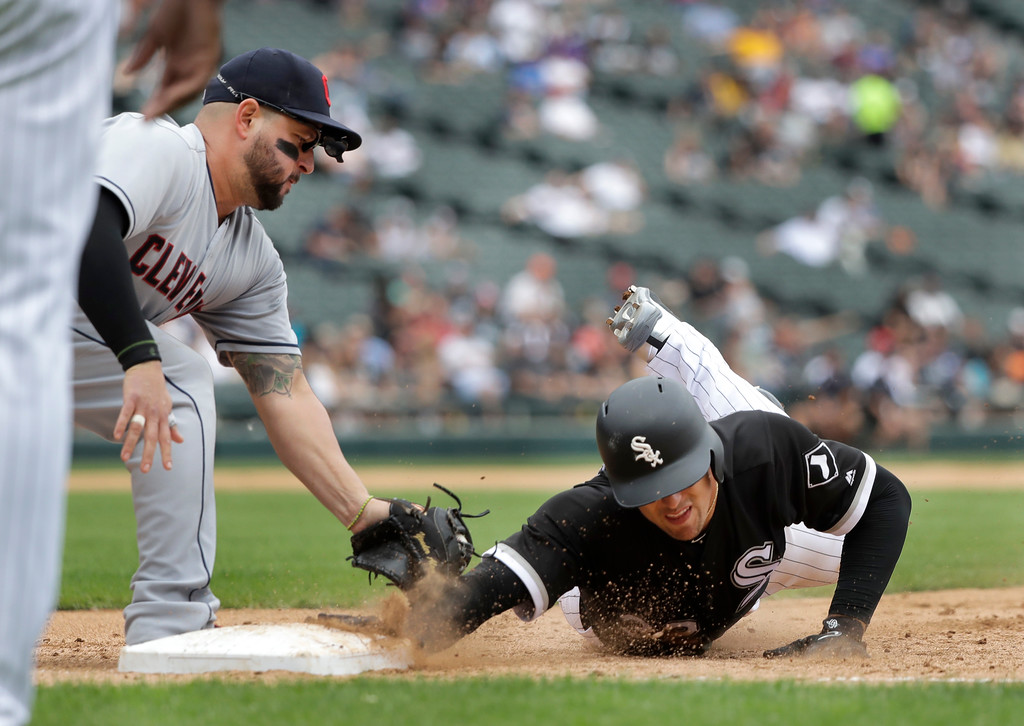 . Chicago White Sox\'s Trayce Thompson, right, dives back to first on a pick-off attempt by Cleveland Indians starting pitcher Mike Clevinger to first baseman Yonder Alonso, left, during the fifth inning of a baseball game Thursday, June 14, 2018, in Chicago. (AP Photo/Charles Rex Arbogast)