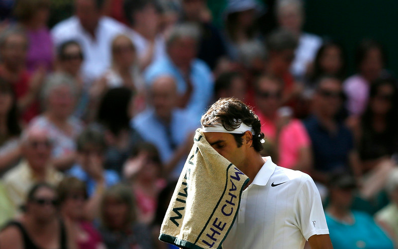 . Roger Federer of Switzerland wipes his face with a towel during the men�s singles semifinal match against Milos Raonic of Canada at the All England Lawn Tennis Championships in Wimbledon, London, Friday, July 4, 2014. (AP Photo/Ben Curtis)