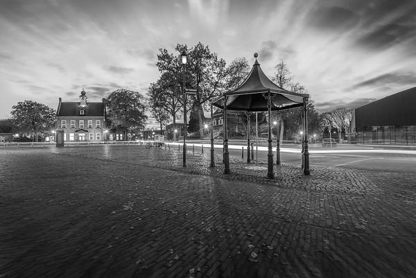 Fine Art architectuur foto in artistiek zwart wit van het centrum van het dorp Nistelrode met het voormalig gemeentehuis en prieel en pomp aan het Laar bij de bibliotheek.