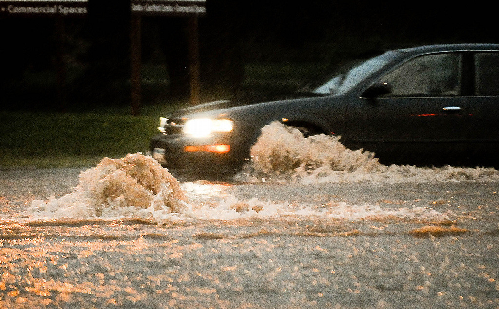 . A water main gushed in the middle of the street as cars made their way through deep water on the corner of Stinson and Broadway in Minneapolis. (Pioneer Press: Ben Garvin)