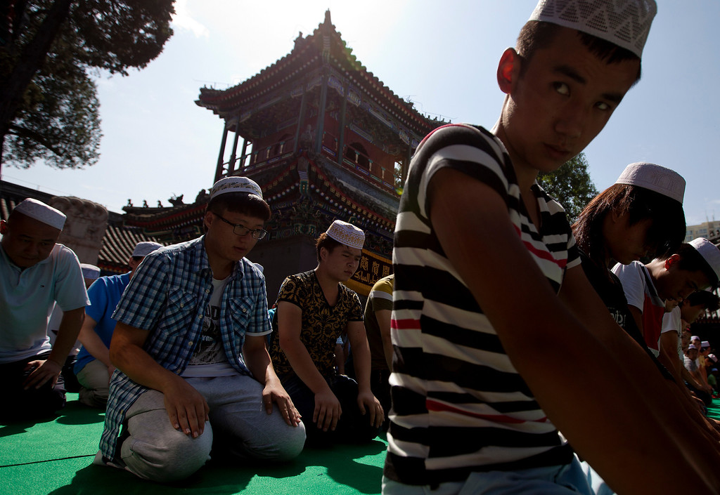 . Muslims offer Eid al-Fitr morning prayer at the Niujie Mosque in Beijing, China Thursday, Aug. 8, 2013. Muslims in China celebrate the Eid al-Fitr that marks the end of the holy fasting month of Ramadan. (AP Photo/Andy Wong)