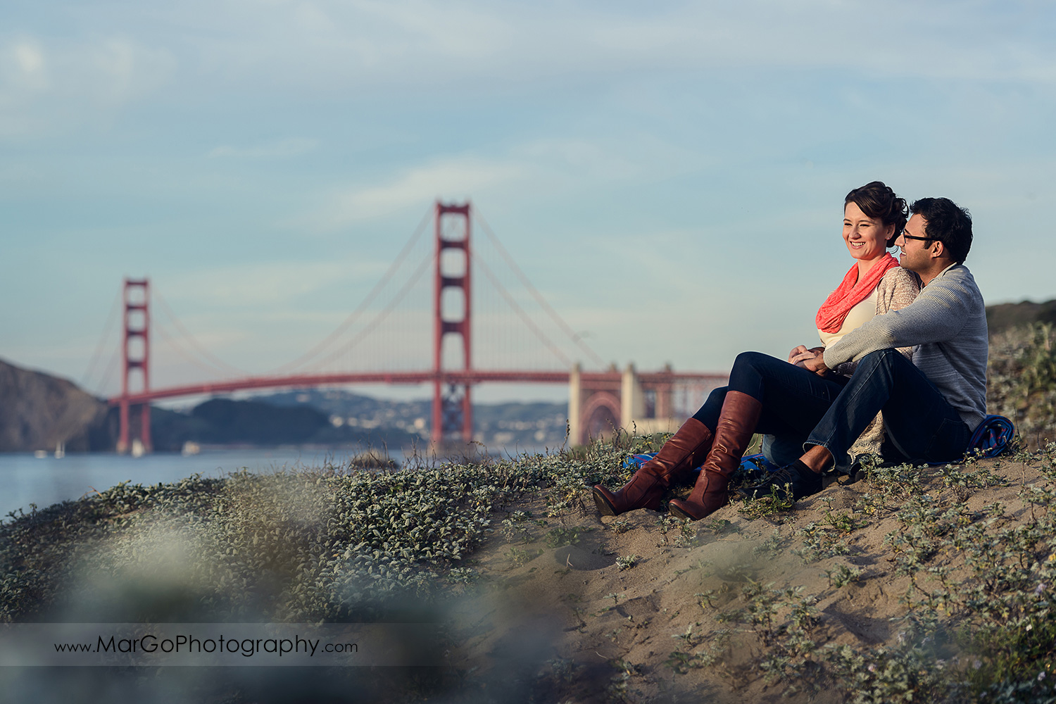 man and woman in grey sweater and jeans sitting on the sand with Golden Gate Bridge in background during engagement session at San Francisco Baker Beach