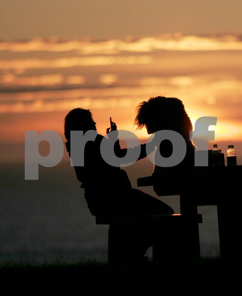 A woman at sunset sitting on a picnic table and using a cell phone to take a photo of her  dog at Ecola State Park near Cannon Beach, Oregon.